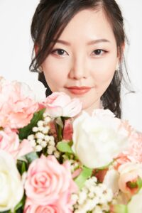 Chelsea's makeup work. An Asian woman looking at the camera and there are flowers in front of her.